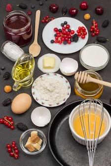空の鍋と泡立て器。小麦粉、壊れた卵、ベリーミルク、バター、ハニージャム。朝食を調理するための材料。フラットレイ