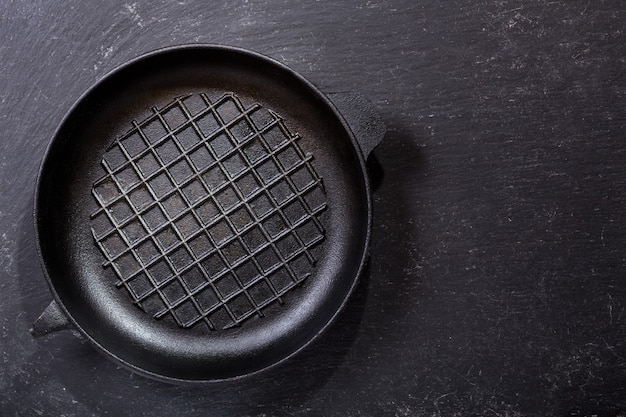 Empty pan on a dark table, top view