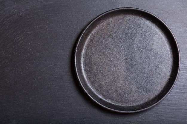 Пустая кастрюля на темном столе, вид сверху Premium Фотографии