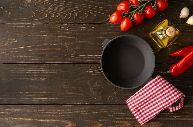 갈색 나무 배경에 빈 팬, 마늘과 고추를 넣은 신선한 육즙 토마토, 병에 든 올리브 오일, 아침 식사 재료, 위쪽 전망, 복사 공간