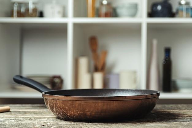 Пустая кастрюля на кухонном столе. посуда на размытие кухонной комнаты