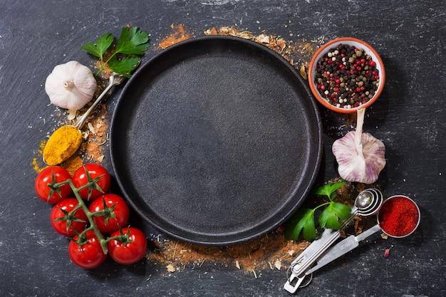 Пустая кастрюля с различными продуктами для приготовления пищи на темном фоне, вид сверху Premium Фотографии
