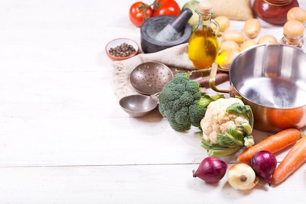 Пустая кастрюля с различными продуктами для приготовления пищи на деревянном столе, вид сверху с копией пространства