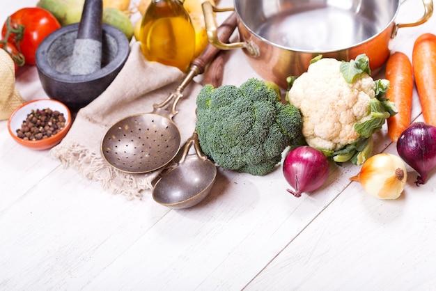 Пустая кастрюля с различными продуктами для приготовления пищи на деревянном столе, вид сверху с копией пространства Premium Фотографии
