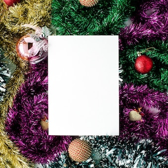 Empty paper blank and christmas decoration with colored glass balls, tinsel, toys. flat lay, top view