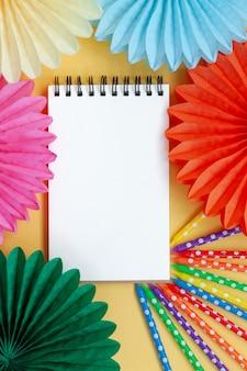空の紙の空白、パステルイエローの誕生日やパーティーのお祝いの誕生日のカラフルなキャンドルと紙のファン