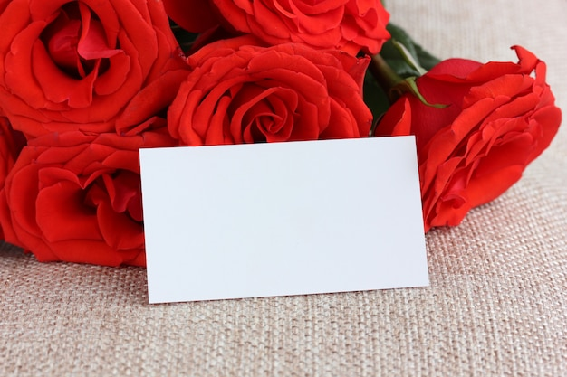 Empty paper card close-up and red roses