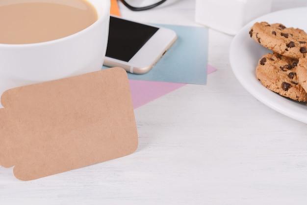 Пустая бумажная карточка с кофе, телефоном и печеньем