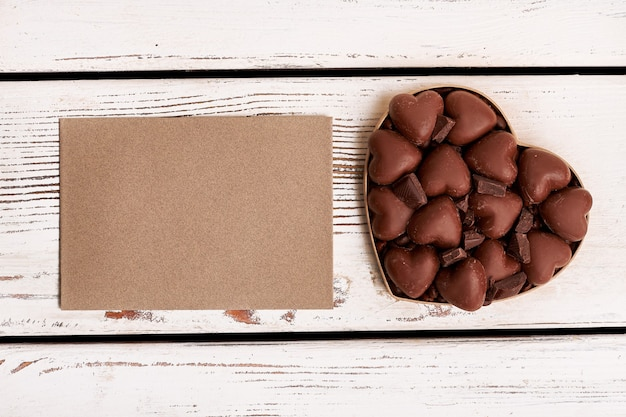 Empty paper and chocolate. confection on wooden background. wish from bottom of heart.