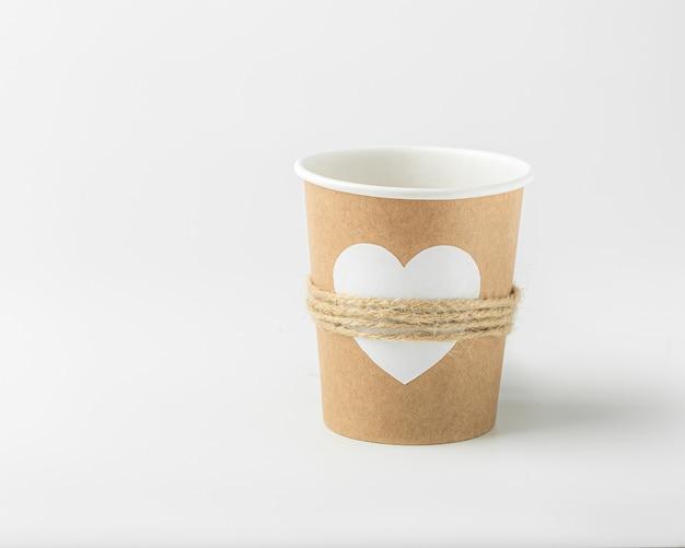 Пустой бумажный стаканчик, украшенный белым сердцем и джутовой нитью на белом