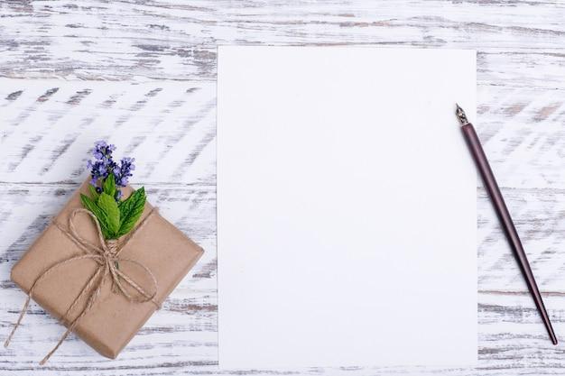 Пустая бумага, цветок, чернильная ручка и подарок на белом деревянном столе. flat lay