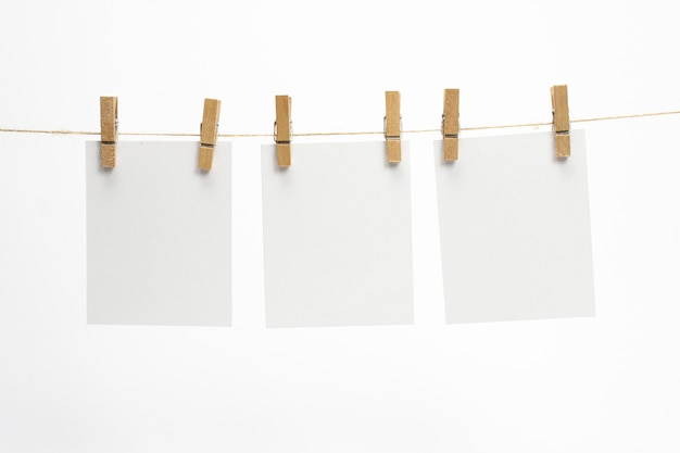 Empty paper frames that hang on a rope with clothespins and isolated on white. blank cards on rope.