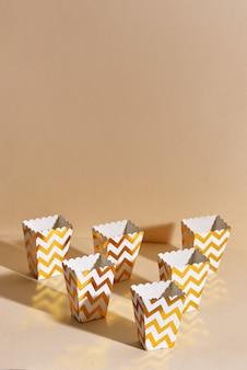 ベージュの壁に新年のクリスマスの装飾と友達との冬休みの会議のための空の紙の黄金のクリスマスカップ