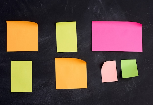 Empty paper multi-colored stickers are glued on a black board