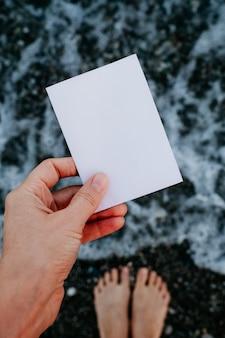 Пустая бумажная записка в руке на фоне удивительного пейзажа. концепция путешествий и отдыха.