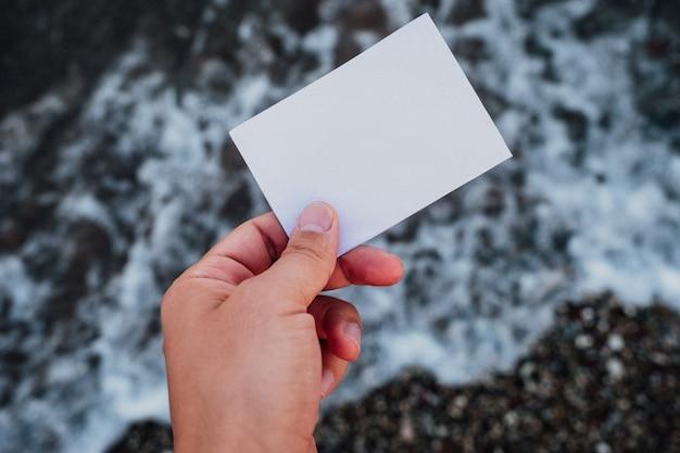 素晴らしい風景の背景で手に空の紙のメモ。旅行と休暇のコンセプト。