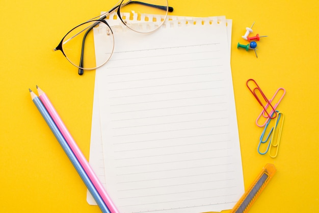 Empty paper of notebook eyeglasses and pencil on color background.