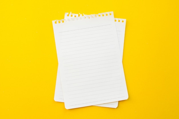 Empty paper of notebook on yellow background with school concept.