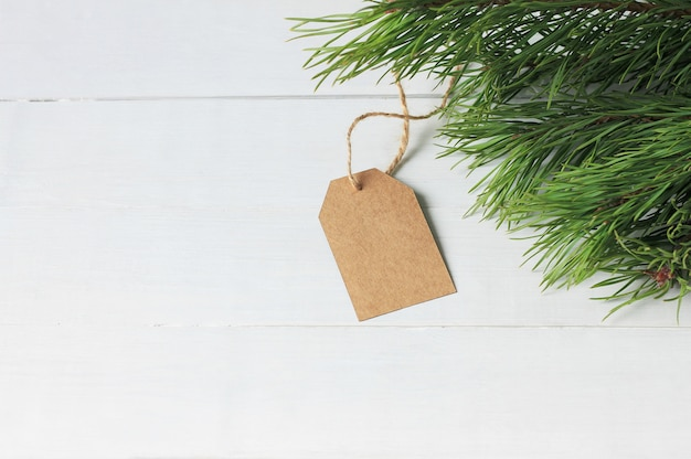 Empty paper price tag, spruce branches on wooden background