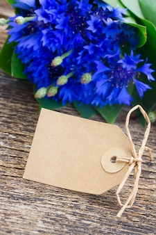 Empty paper tag with blue fresh cornflowers on wooden table
