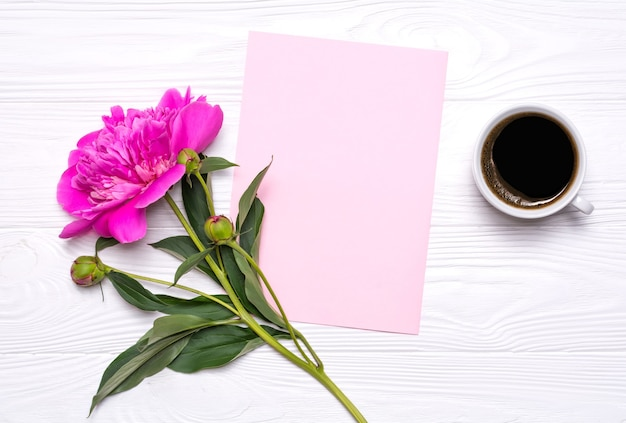 Empty paper with place for text, a cup of coffee and peony flower