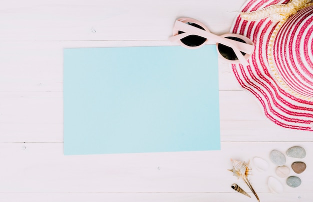 Empty paper with summer accessories on light background