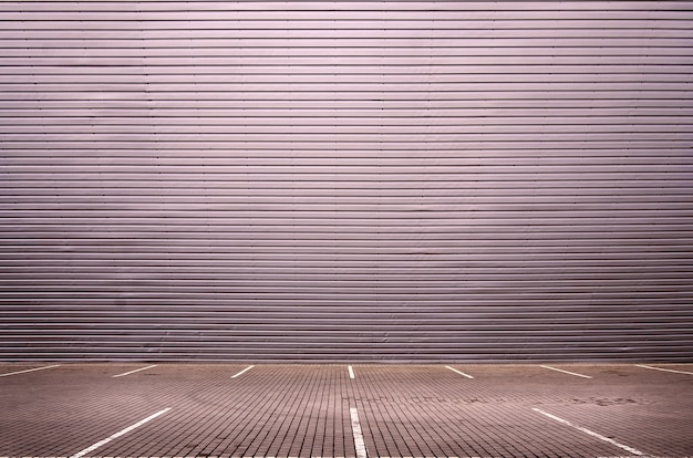 Пустые парковочные места на фоне металлической стены с местом для размещения товара