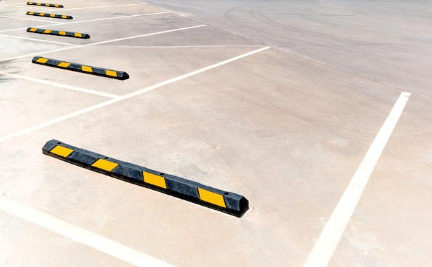 Empty parking stalls in a parking lot, marked with white lines.