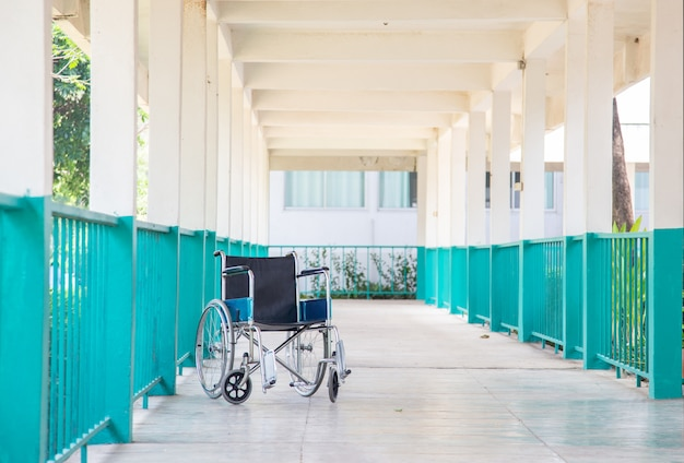 Empty patient wheelchair on walking way at hospital
