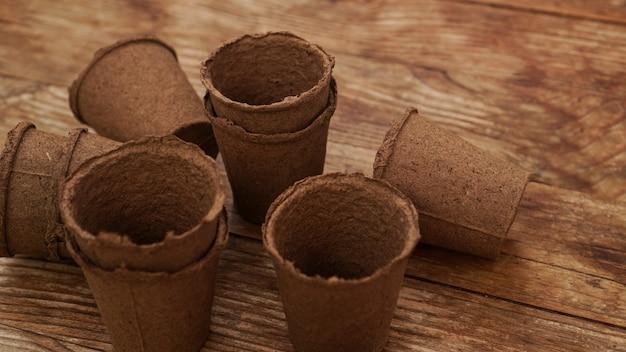 Пустые торфяные горшки для рассады на деревянном фоне. садоводство. концепция подготовки садового инвентаря к весенней посадке растений и цветов