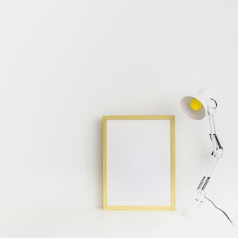 Empty photo frame and desk lamp