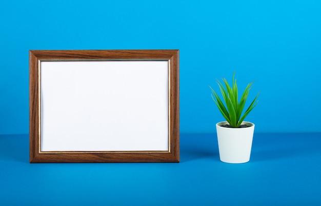 Пустая рамка для фотографий и цветок на столе. синяя стена.