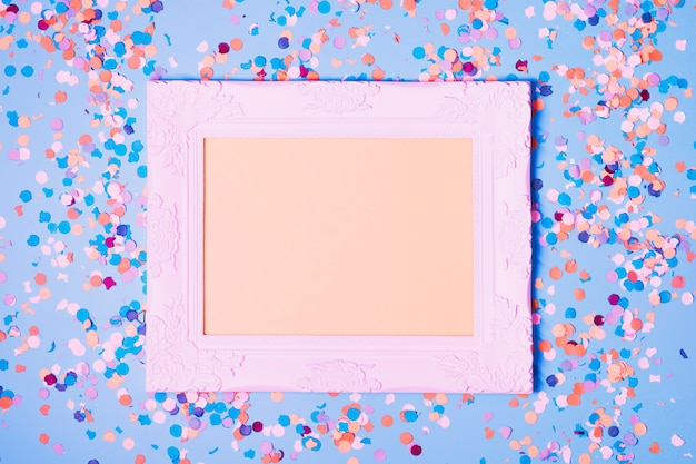 Empty photo frame and decorative confetti on blue background