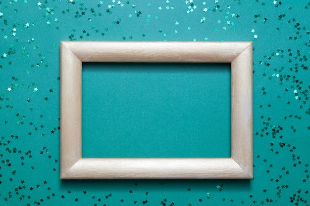 Empty photo frame mock up with many green shiny stars on green paper background