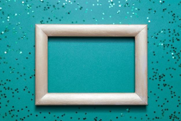 녹색 종이 배경에 많은 녹색 빛나는 별을 모의 빈 사진 프레임