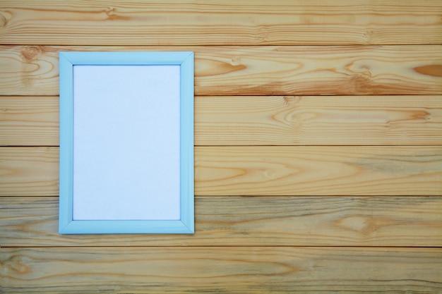 가벼운 나무 테이블에 빈 사진 프레임, 공간을 복사하기 위해 사진을 추가하는 모형.