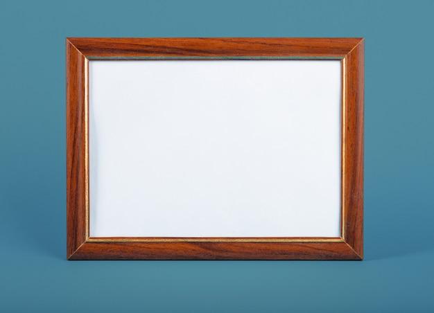 Пустая рамка для фотографий на столе. синяя стена.