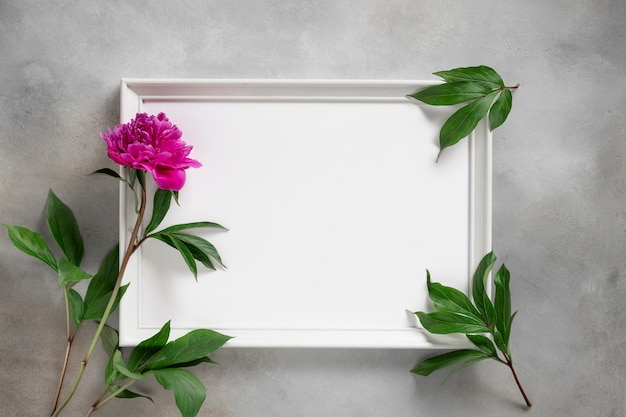 Empty photo frame and purple peony and leaves