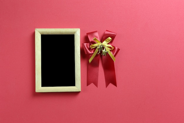 Empty photo frame and red bow