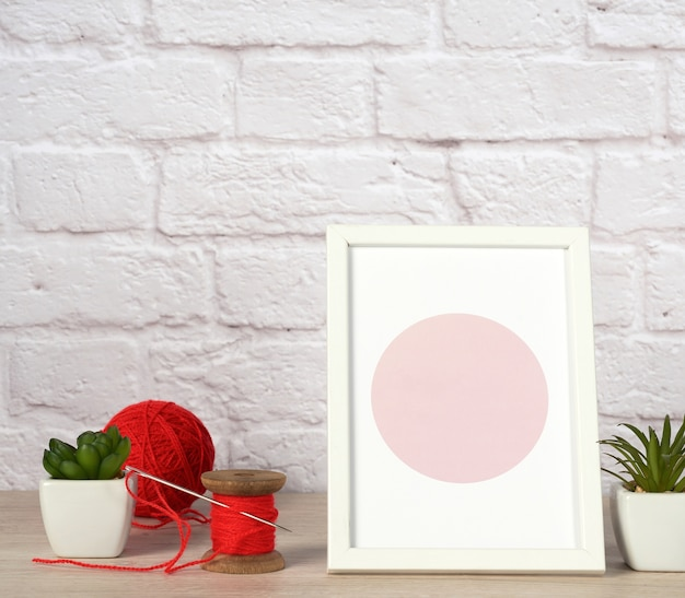 Empty photo frame, succulents to a white ceramic pot and a red ball with woolen thread