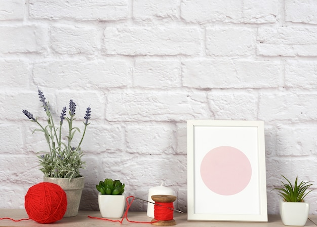 Empty photo frame, succulents to a white ceramic pot and a red ball