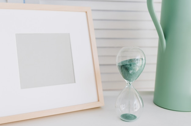 Empty photo frame, watering pot and a running hourglass or sand clock