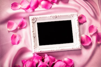 Empty photo frame with a bouquet sweet pink roses  petal on soft pink silk fabric