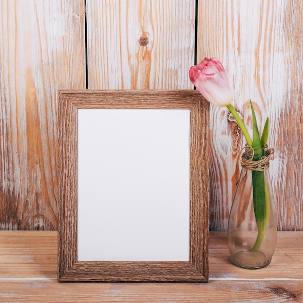 Empty photo frame with single tulip flower in vase on wooden background