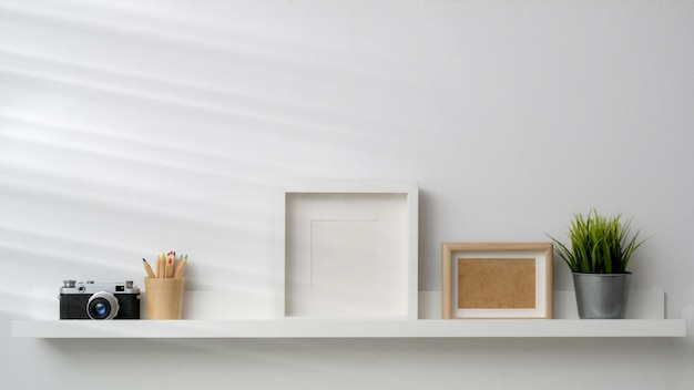 Empty photo frames, camera and decorations on white shelf with white wall