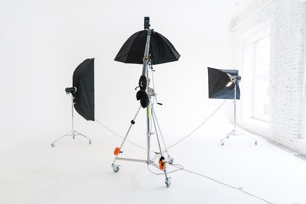 조명 장비와 빈 사진 스튜디오입니다. 전문 도구 세트 장비와 사진 작가 직장 인테리어. 플래시 조명, 흰색 배경 장면 스튜디오 촬영 준비. 현대 사진 스튜디오