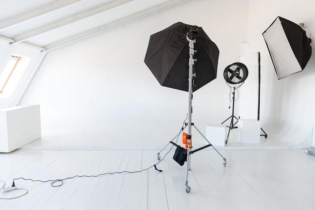 조명 장비가 있는 빈 사진 스튜디오. 전문 도구 세트 장비가 있는 사진 작가 작업장 인테리어입니다. 플래시 라이트, 스튜디오 촬영을 위해 준비된 흰색 배경 장면. 현대 사진 스튜디오