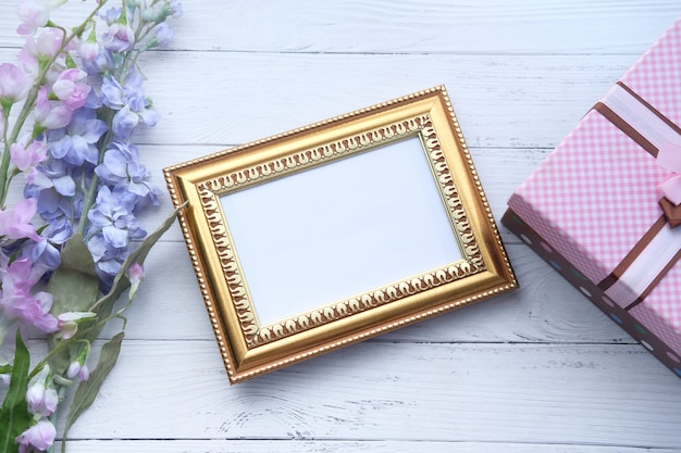 Empty picture frame, gift box and flower on table.