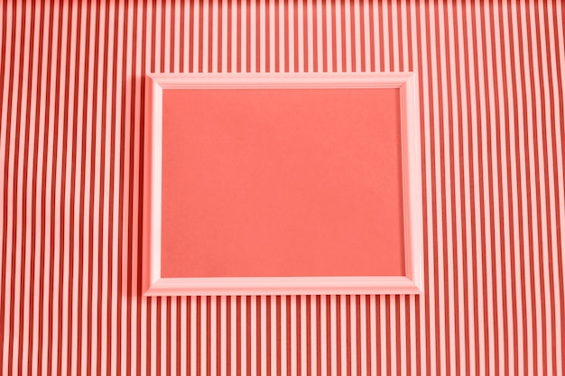 Empty picture frame mock up on coral and white striped background.