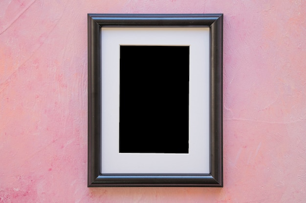 An empty picture frame on pink painted wall